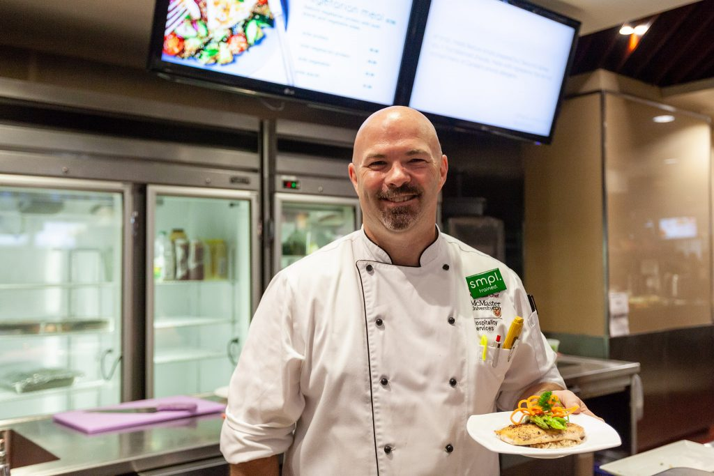 Photo of chef smiling holding plate of salmon and asparagus