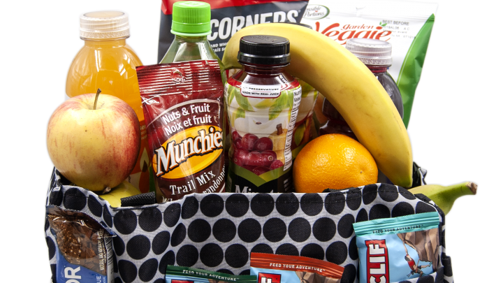 close up shot of care package bag filled with fruit and bottled beverages