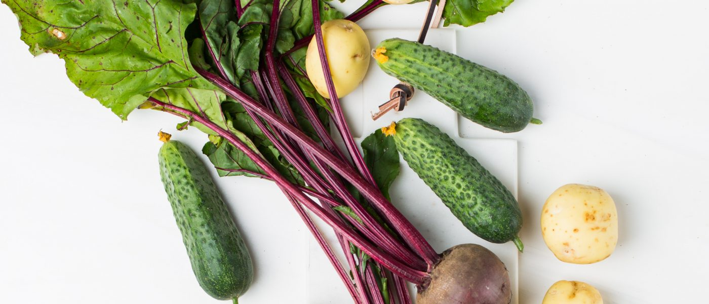 raw beets with leaves and cucumbers. top down view on table