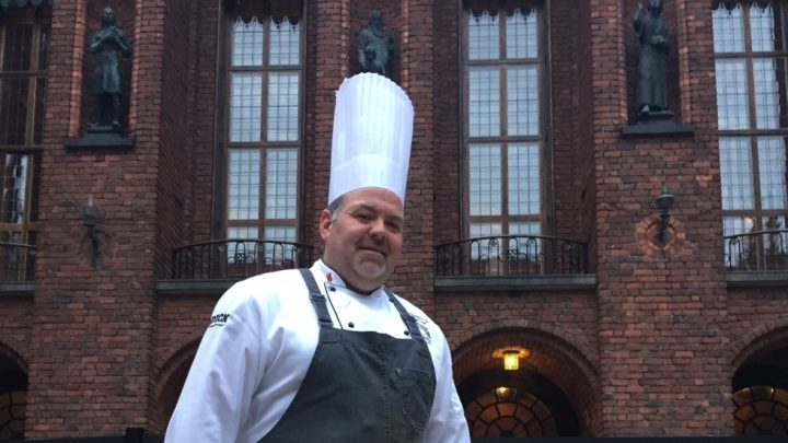 picture of a chef from upward angle in front of building